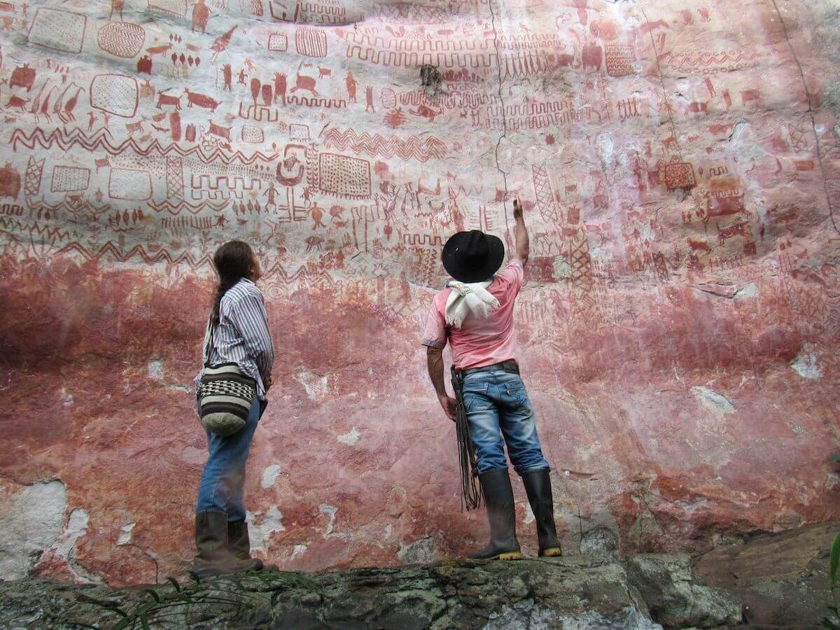 Personas ante las pinturas de la serranía de Lindosa.